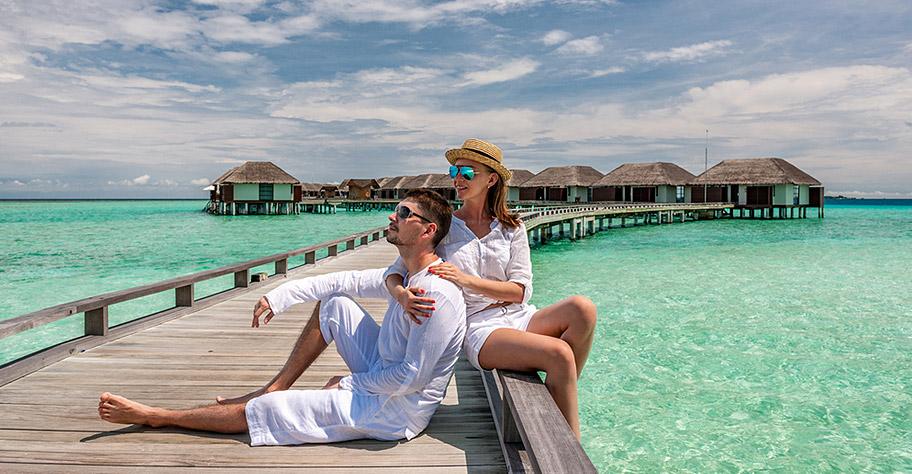 Paar vor Wasserbungalow Malediven Hochzeitsreise